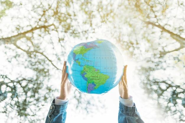 Modelo de planeta inflável nas mãos na natureza