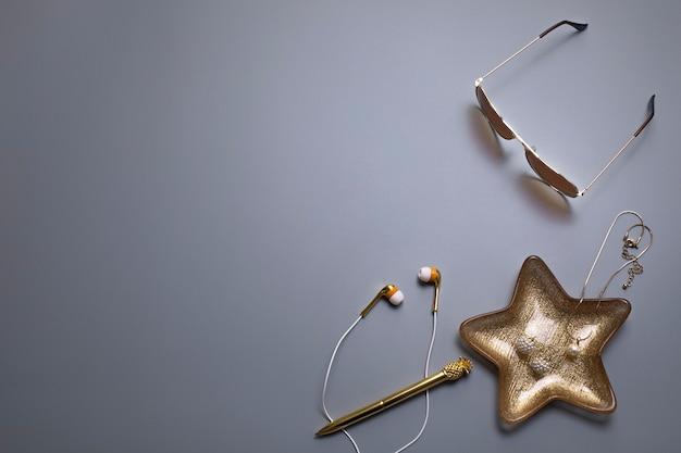 Modelo de plano de fundo elegante para texto ou logotipo óculos de sol, fones de ouvido e joias em fundo cinza