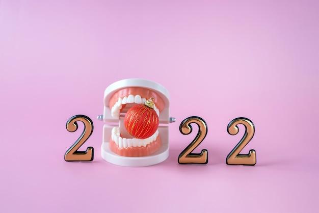 Modelo de plástico de uma mandíbula humana, uma bola de natal e os números 2022