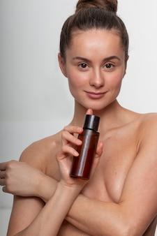 Modelo de produto de beleza mulher parede branca cuidados com a pele spa publicidade