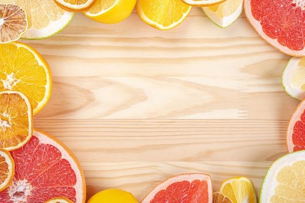 Modelo de quadro de citros em fundo de madeira. frutas cítricas frescas. vista superior de frutas cítricas fatiadas.