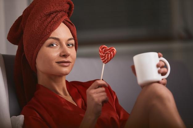 Modelo de roupão vermelho e toalha vermelha no sofá com uma caneca de café e um pirulito.