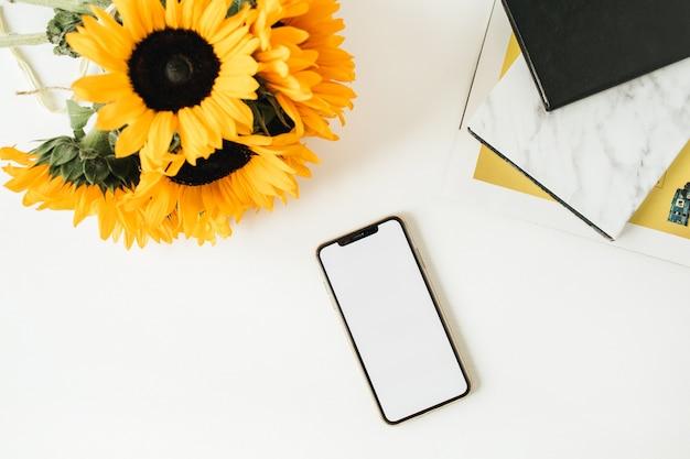 Modelo de telefone com tela de maquete de espaço de cópia e buquê de girassóis amarelos sobre fundo branco. flatlay.
