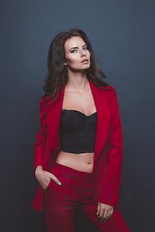 Modelo de terno vermelho. mulher jovem posando com um terno vermelho sobre cinza