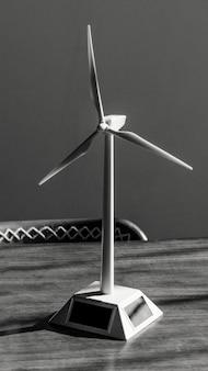 Modelo de turbina eólica solar em uma mesa de madeira em tons de cinza