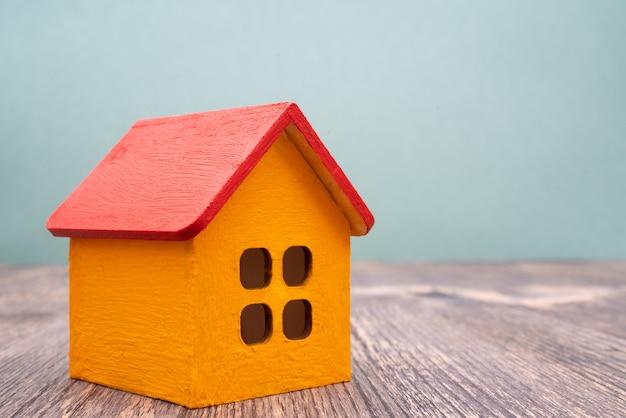Modelo de uma casa de madeira amarela com telhado vermelho. aluguer e venda de edifícios e casas. Foto Premium