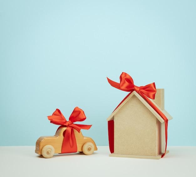 Modelo de uma casa de madeira e um brinquedo de carro amarrado com uma fita de seda vermelha, conceito de compra de imóveis, hipoteca. copie o espaço