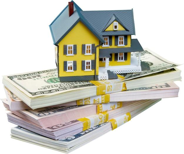 Modelo de uma casa em uma pilha de dinheiro - isolada