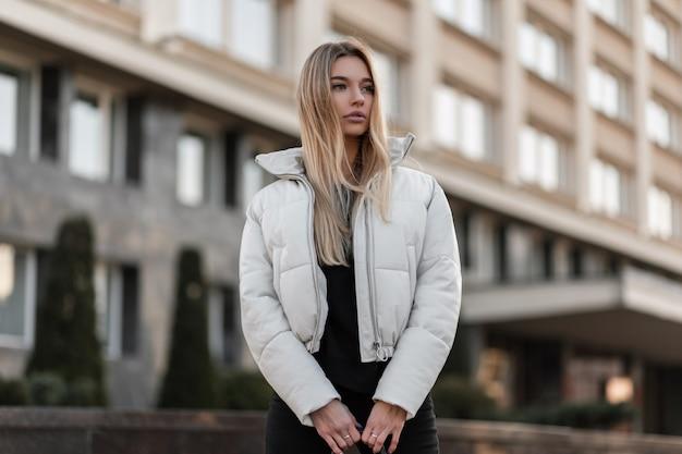 Modelo de uma jovem com uma jaqueta branca e uma bolsa de couro da moda fica na cidade