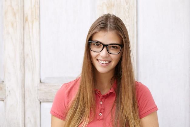 Modelo de uma linda mulher usando óculos retangulares posando na parede de madeira