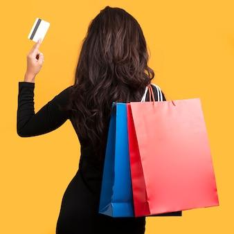 Modelo de venda de sexta-feira negra segurando um cartão de crédito por trás da foto