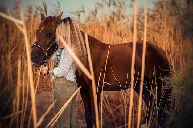 Modelo de vestido branco, andando com um cavalo