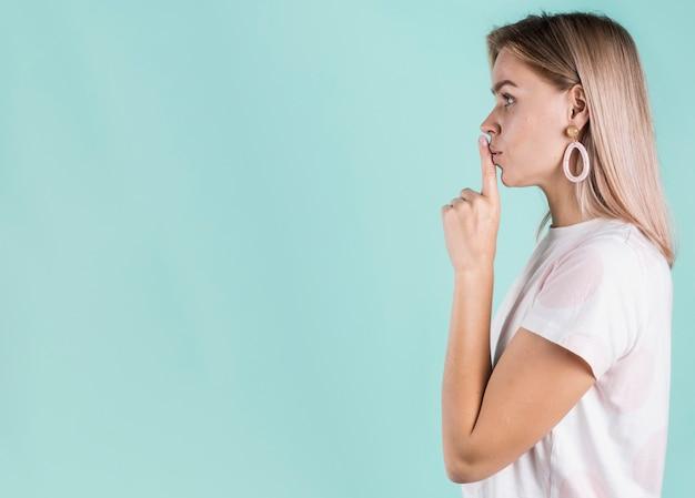 Modelo de vista lateral gesticulando sinal de silêncio