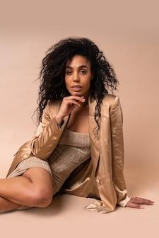 Modelo deslumbrante bronzeado com penteado encaracolado volumoso em vestido dourado brilhante e blazer de cetim sentado no chão bege
