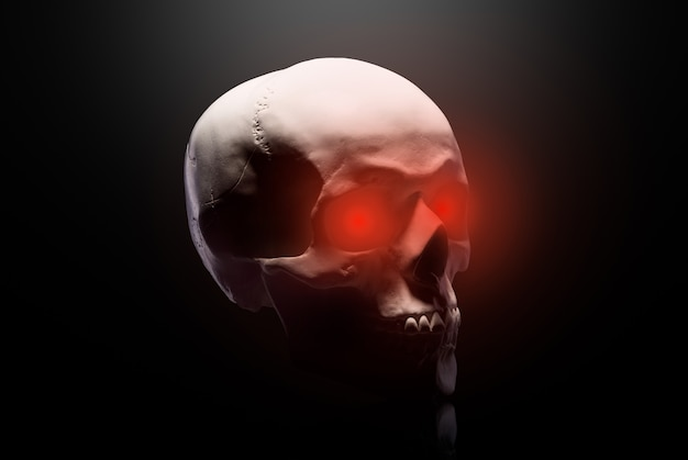 Modelo do crânio humano com olhos vermelhos isolado em fundo preto