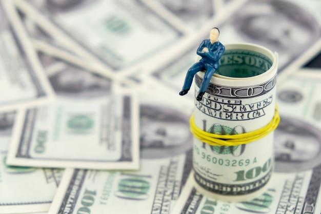 Modelo do homem do brinquedo que senta-se em um pacote de dinheiro em um fundo preto.