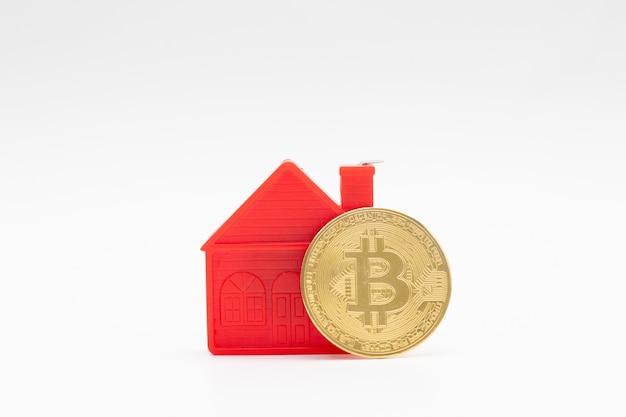 Modelo do modelo de casa pequena vermelha e moeda de ouro bitcoin sobre fundo branco.