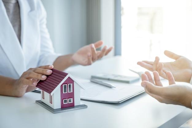 Modelo doméstico. o corretor de imóveis explica o contrato comercial, o aluguel, a compra, a hipoteca, o empréstimo ou o seguro da casa ao comprador feminino.