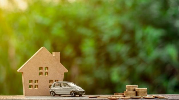 Modelo e moedas diminutos cinzentos do carro na tabela de madeira.