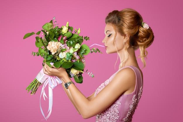 Modelo elegante, cheirando um perfume em branco