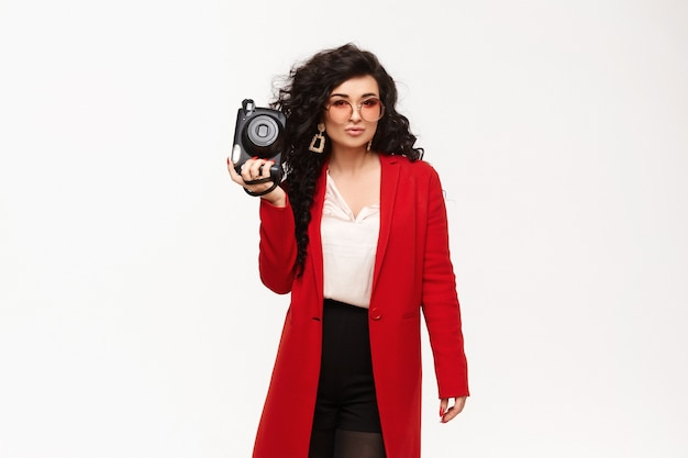 Modelo elegante com casaco vermelho, brincos grandes de ouro e óculos de sol redondos posando com uma câmera velha na mão
