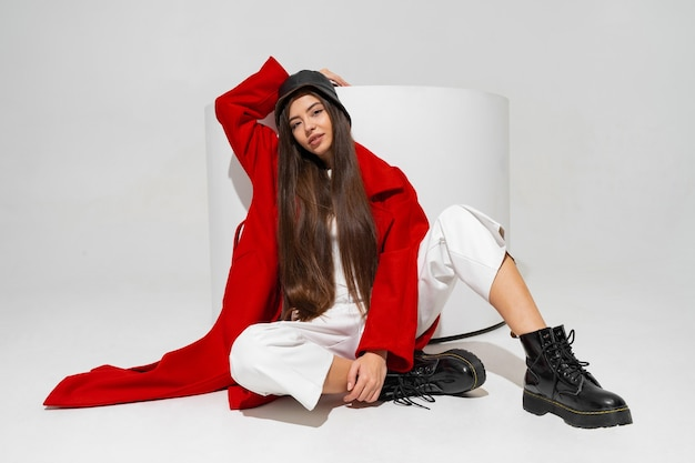 Modelo elegante com chapéu elegante, casaco vermelho e botas posando na parede branca do estúdio