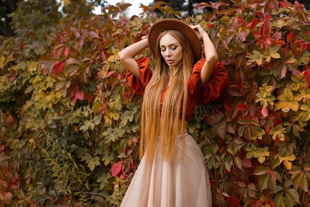 Modelo elegante com um chapéu marrom com cabelo comprido perto das folhas vermelhas em close-up de outono