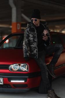 Modelo elegante de homem bonito com óculos escuros e chapéu em uma elegante jaqueta militar de inverno com pulôver e jeans perto de um carro vermelho na rua
