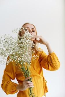 Modelo elegante em uma blusa amarela com flores brancas secas e maquiagem da moda
