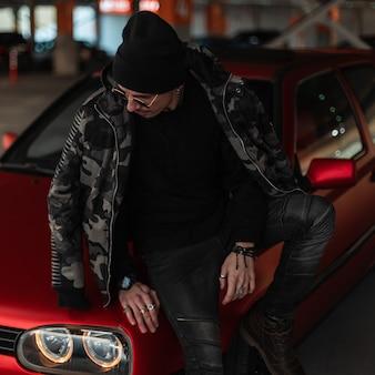 Modelo elegante jovem bonito com óculos escuros e um chapéu em uma jaqueta militar elegante de inverno fica perto de um carro vermelho na rua