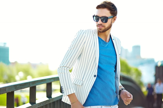 Modelo elegante jovem confiante feliz empresário elegante em roupas hipster de terno andando na rua em óculos de sol