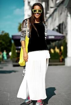 Modelo elegante mulher jovem e bonita morena em roupas casuais coloridas de hipster de verão posando na rua fundo