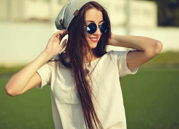 Modelo elegante mulher jovem e bonita morena em roupas casuais de hipster de verão posando na rua fundo no parque