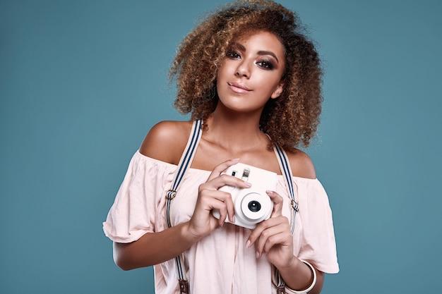 Modelo elegante mulher negra com cabelo encaracolado e câmera
