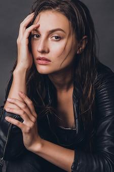 Modelo elegante posando em estúdio com roupas elegantes e tendência de estilo de couro de rock