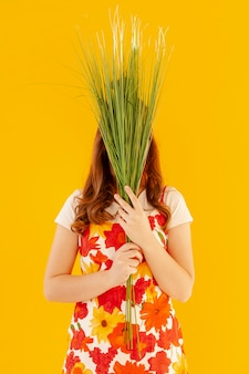 Modelo elegante segurando plantas vista frontal