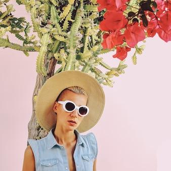 Modelo em acessórios de verão da moda e roupa jeans em cactos local viagem clima de praia