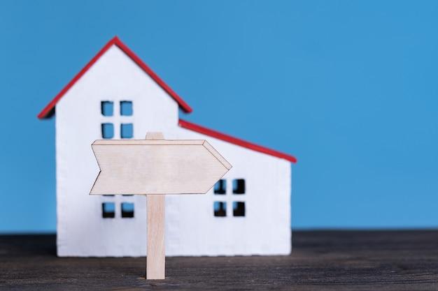 Modelo em casa com placa de madeira. comprando o conceito de casa.