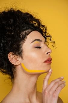 Modelo em close-up posando com maquiagem amarela