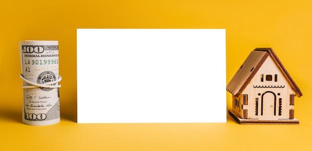 Modelo em miniatura da casa e dinheiro com fundo em branco sobre fundo amarelo. investimento, imobiliário, casa, habitação