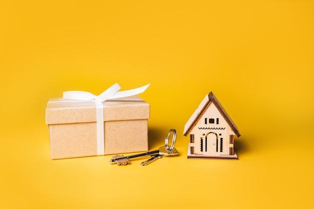 Modelo em miniatura da casa, presente e chaves em um fundo amarelo. investimento, imobiliário, casa, habitação