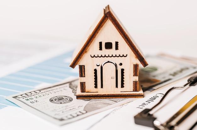 Modelo em miniatura de casa e dinheiro em documentos