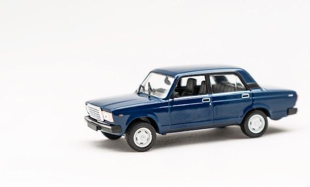 Modelo em miniatura de um carro retrô azul de brinquedo em uma superfície branca