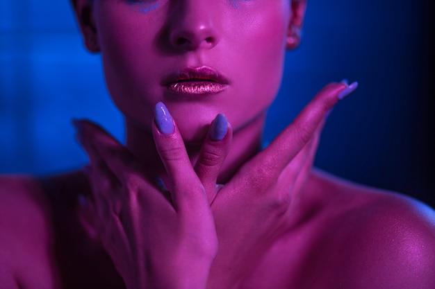Modelo em tons de neon com lábios brilhantes para manter as mãos perto do rosto.