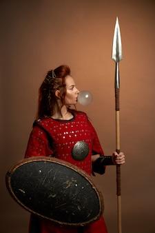 Modelo em traje medieval posando, soprando chiclete.