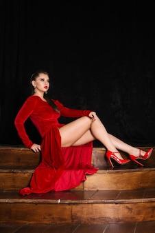 Modelo em um vestido vermelho sexy sentado em degraus de madeira