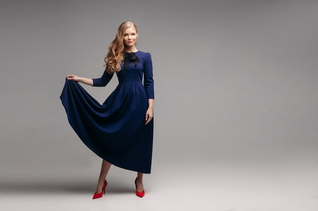 Modelo esbelto deslumbrante em vestido azul brilhante e salto preto.