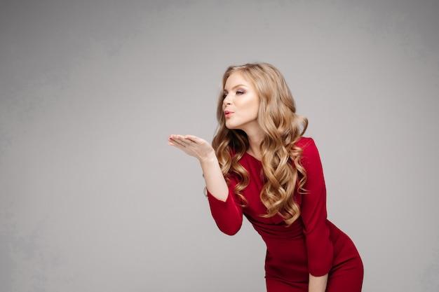 Modelo esbelto deslumbrante em vestido vermelho brilhante e salto preto.