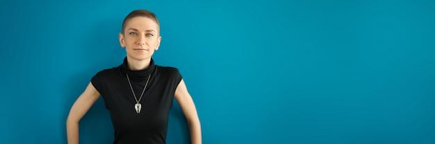 Modelo esguio de aparência europeia com medalhão posado contra a parede. mulher de vestido preto com corte de cabelo curto
