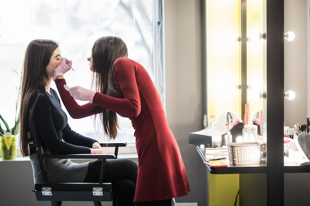 Modelo está sentado na cadeira alta durante o procedimento de maquiagem profissional